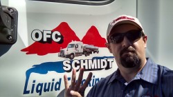 Liquid Trucking driver selfie, holding up 4 fingers next to truck